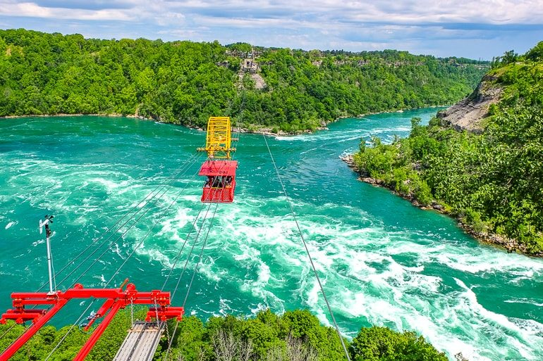 red cable car over white water in niagara river aero car ride things to do
