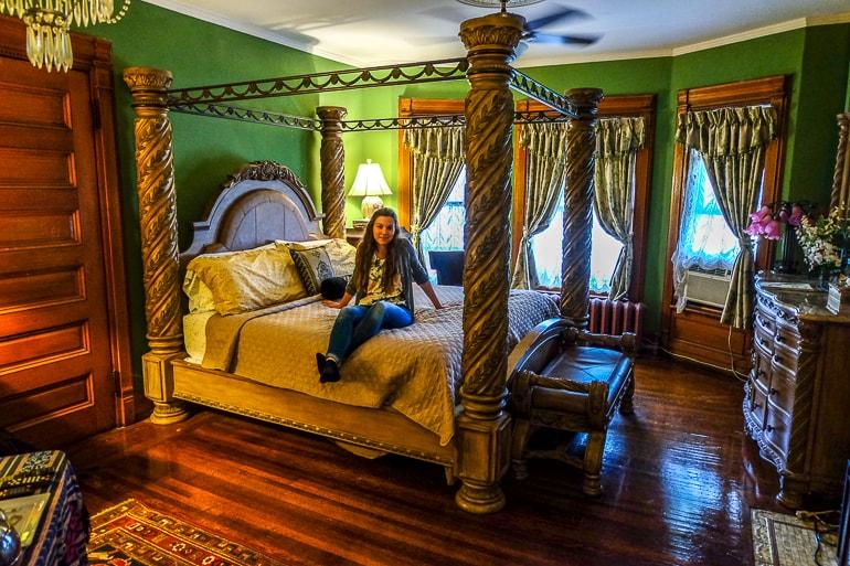 Frau sitzt auf großem Bett in antikem Zimmer in Niagara Falls Bed and Breakfast