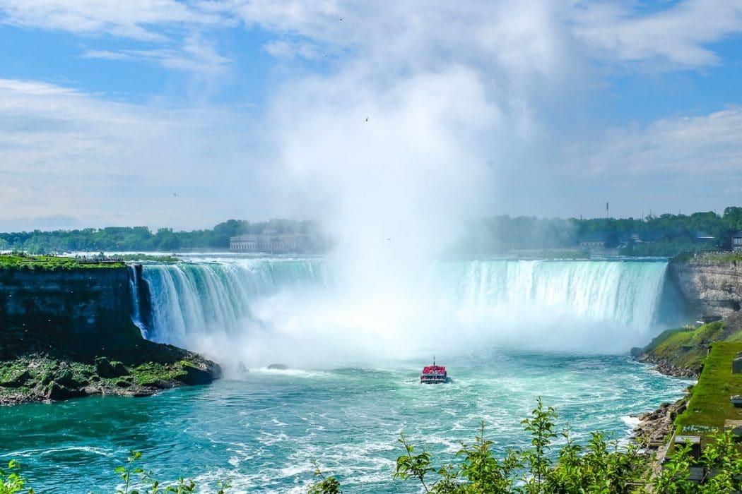 Blaues Wasser und Wasserfälle mit kleinem Boot im Fluss darunter Niagara Falls Kanada
