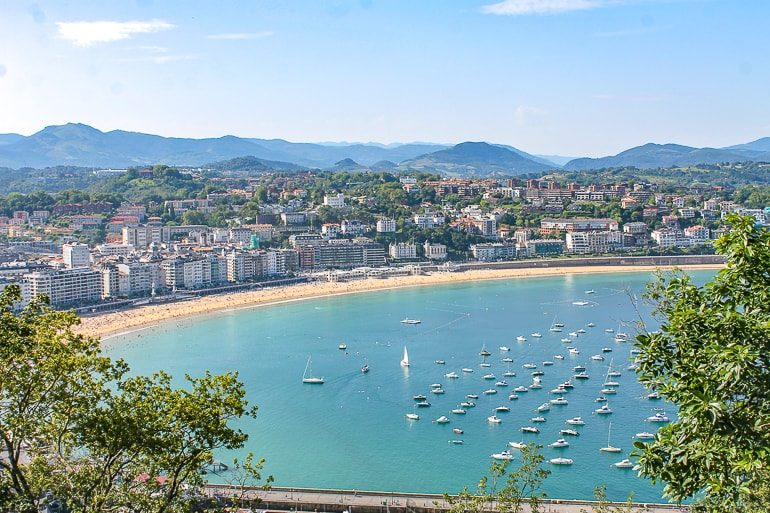 blue bay with boats and sandy beach around it with buildings beautiful cities in spain san sebastian