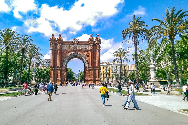 red archway with sidewalk and palm trees around and people barcelona beautiful cities to visit spain