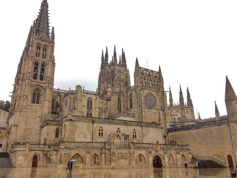 stone cathedral building in rain with reflective ground on front burgos beautiful cities spain