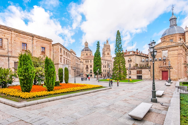 bright public square with gardens and towers behind salamanca spain