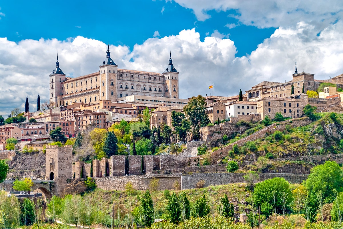 square castle with spires on hillside with green trees below beautiful cities in spain toledo