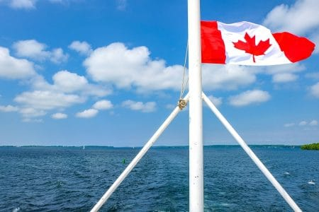canada flag waving in wind at back of ship with blue lake below canada sightseeing