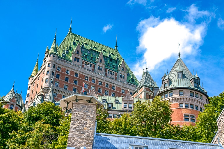 old castle looking hotel with green roof and trees below quebec city