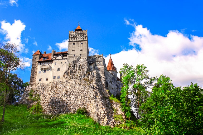 stone castle with red roof and trees around bran castle day trip from brasov