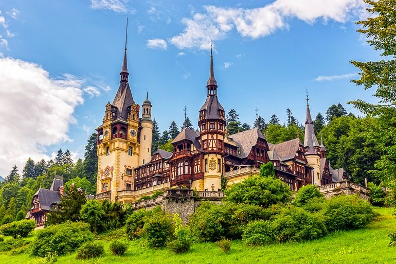 brown and yellow castle with towers and green bushes peles castle day trip from brasov