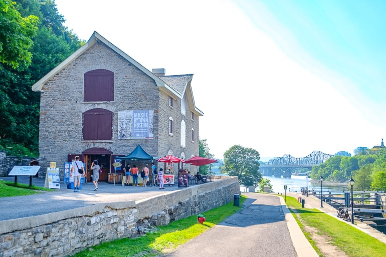 stone house with people beside pathway to river rideau canal