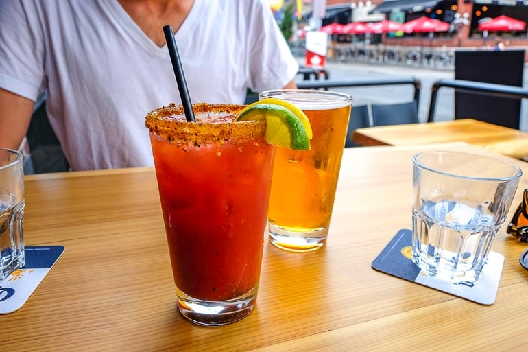 canadian caesar drink with pint of beer on wooden table one day in ottawa