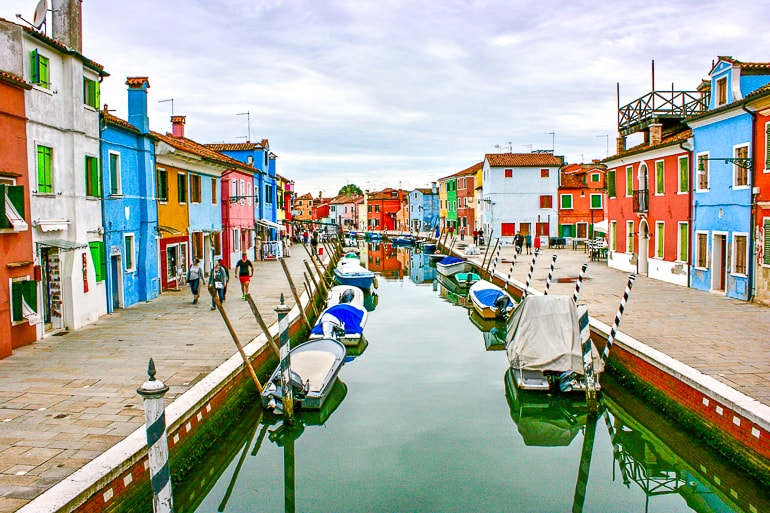 boats in blue canal with colourful houses lining edges burano italy one day