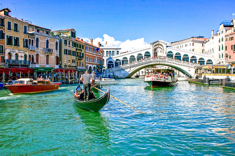bridge over canal with boats in front rialto bridge one day in italy