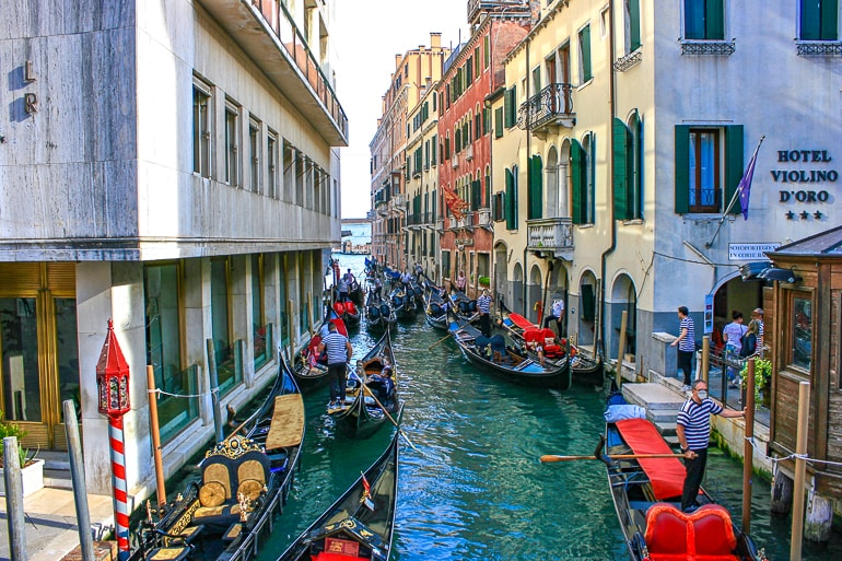 gondola boats with men standing on canal one day in venice italy