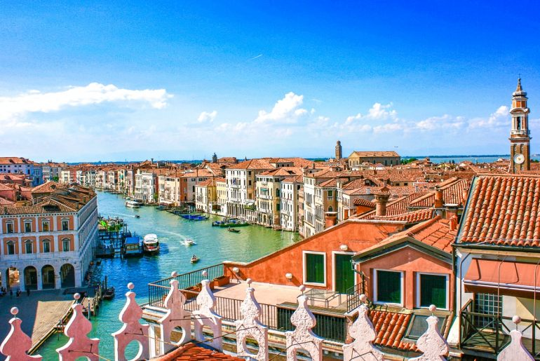 orange roofs and blue canal form above Fondaco dei Tedeschi terrace one day in venice italy