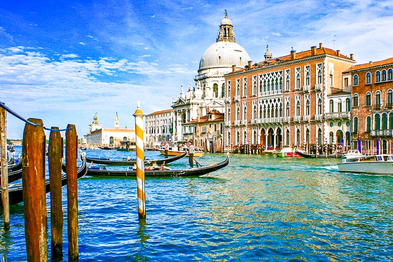 white dome building with brown building beside on canal bank with boats in grand canal one day in venice italy