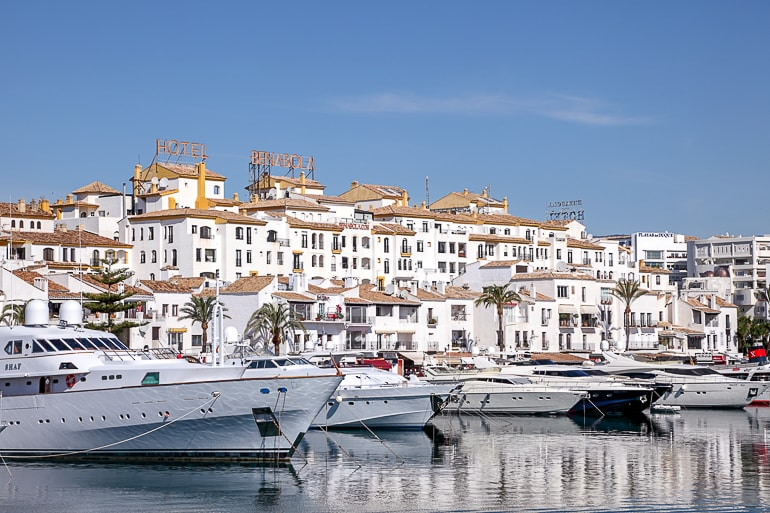 white boats lined up in front of white buildings on land marbella spain itinerary