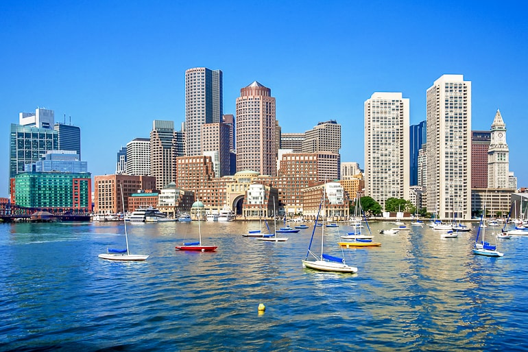 tall buildings at edge of harbour with boats in water things to do in boston