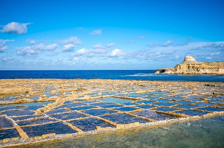 blue square salt pans on shoreline with sea behind things to do in gozo
