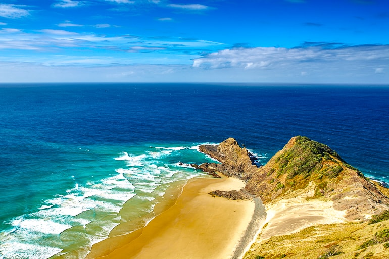 sandy beach point with blue ocean around cape reinga new zealand