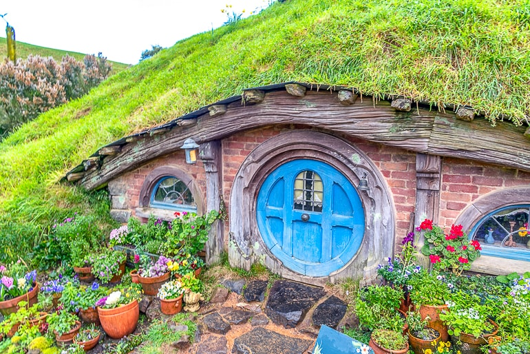 blue wooden door to small house in grassy hillside hobbiton new zealand