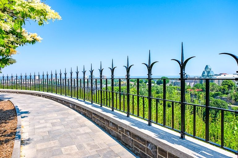 iron fence with stone pathway in front and views behind ottawa river canada
