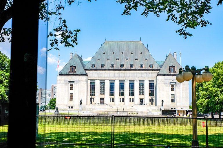 Weißes und graues Gerichtsgebäude mit grünem Gras im Vordergrund Oberster Gerichthof Kanada