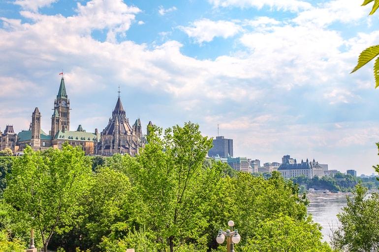 Kanadische Parlamentsgebäude mit grünen Bäumen und Fluss im Vordergrund Sehenswürdigkeiten Ottawa