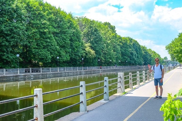man waving on sidewalk beside canal lined with trees rideau canal ottawa