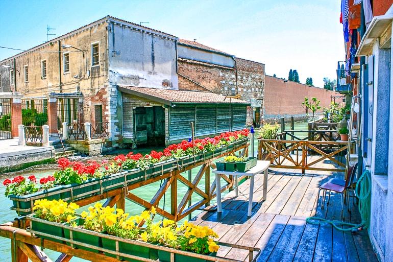 Holzterrasse mit bunten Blumen Kanal und Häuser im Hintergrund Giudecca Italien