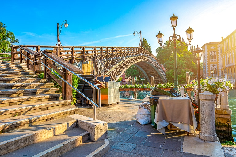 wooden bridge over canal with steps and sunshine venice italy