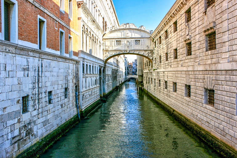 small white bridge between buildings with water below bridge of sighs venice italy