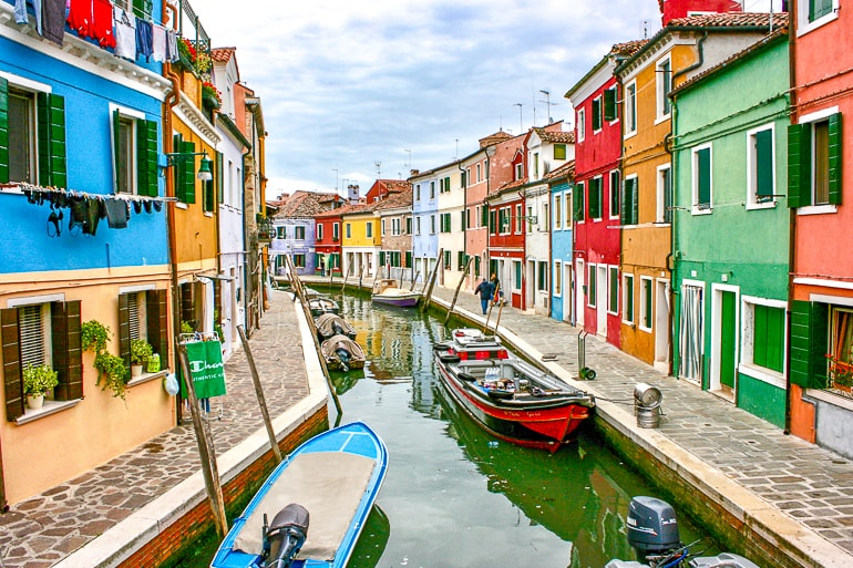 coloured buildings with canal and boats in centre burano italy