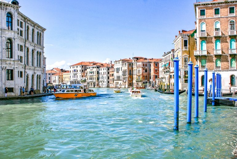 blue canal water with boats and houses beside things to do in venice italy