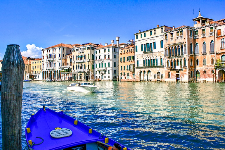 blue boat with canal and houses in behind in venice italy