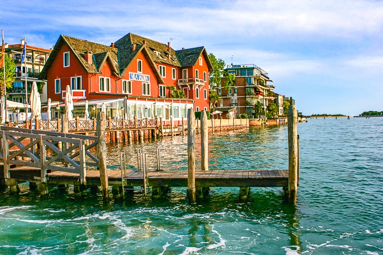 wooden dock with red house behind on seaside lido venice italy