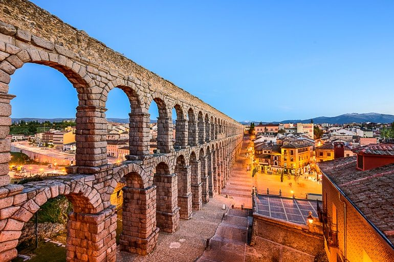 stone arches forming aqueduct with village below top attractions in spain segovia