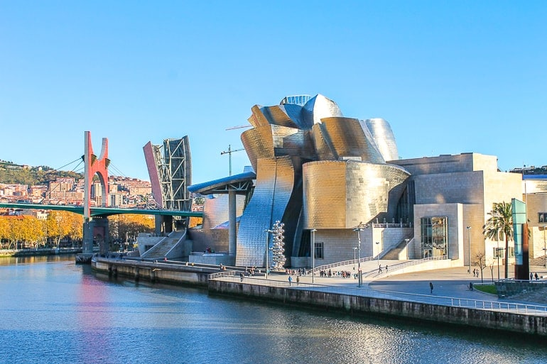 metallic museum exterior by river edge with bridge behind guggenheim bilbao