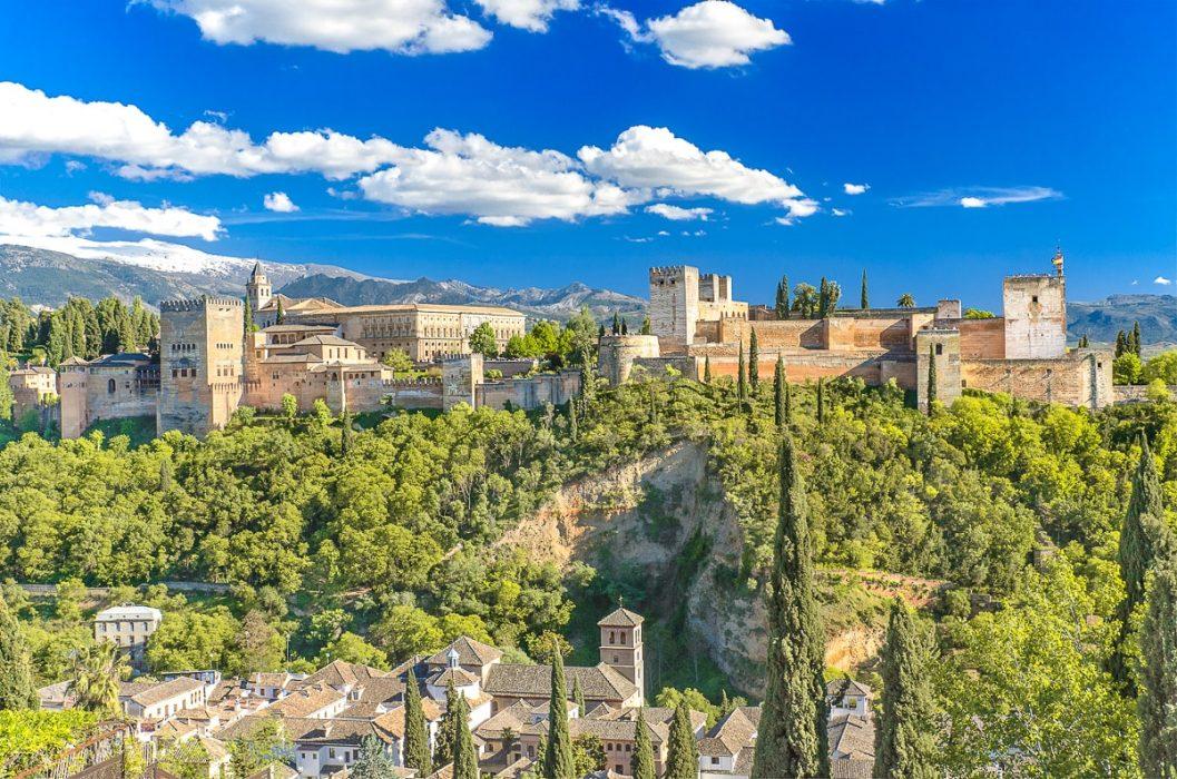Schloss aus Stein auf Hügel mit Sträuchern in Granada Spanien