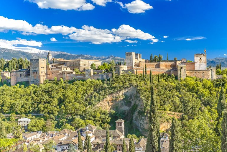 tan stone fortress on hill with green trees below alhambra granada