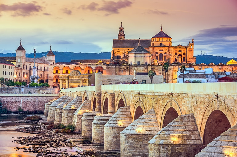 stone bridge leading to orange cathedral on hill cordoba spain top attractions