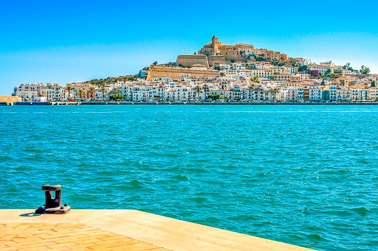 blue ocean water with hilltop city behind dalt vila spain attraction