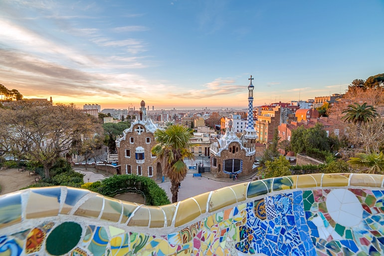 colourful tiles of bench with coloured houses below and sunset guell park barcelona