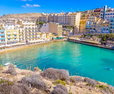 blue bay with hotels and cliffs surrounding gozo accommodations xlendi