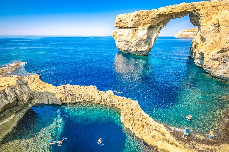 rock arch over blue ocean with people swimming azure window diving site gozo