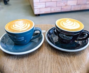 blue and black mugs on wooden stool with coffee art cafes in munich