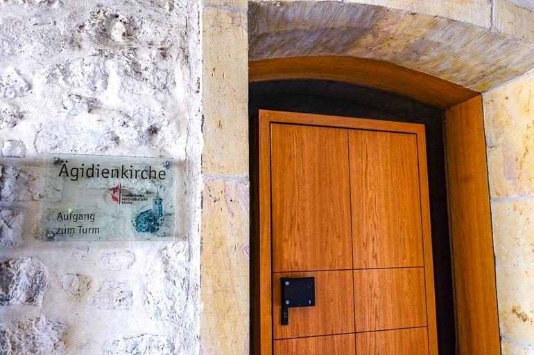 Braune Eingangstür zu Kirche mit weißer Wand