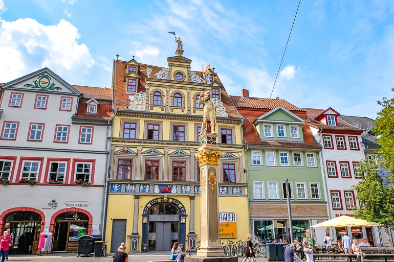 yellow old building with golden statue in front in german square erfurt germany kunsthalle