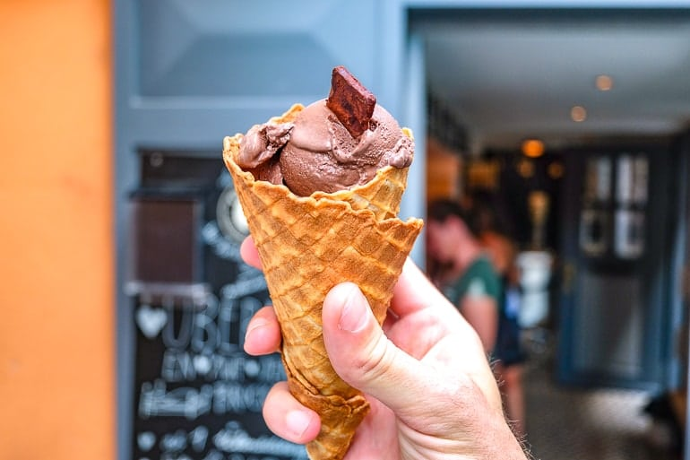 chocolate ice cream cone held in hand