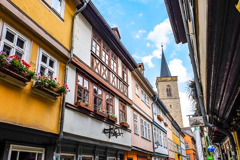 Kirchturm aus Stein im Hintergrund mit bunten Ladenfassaden im Vordergrund
