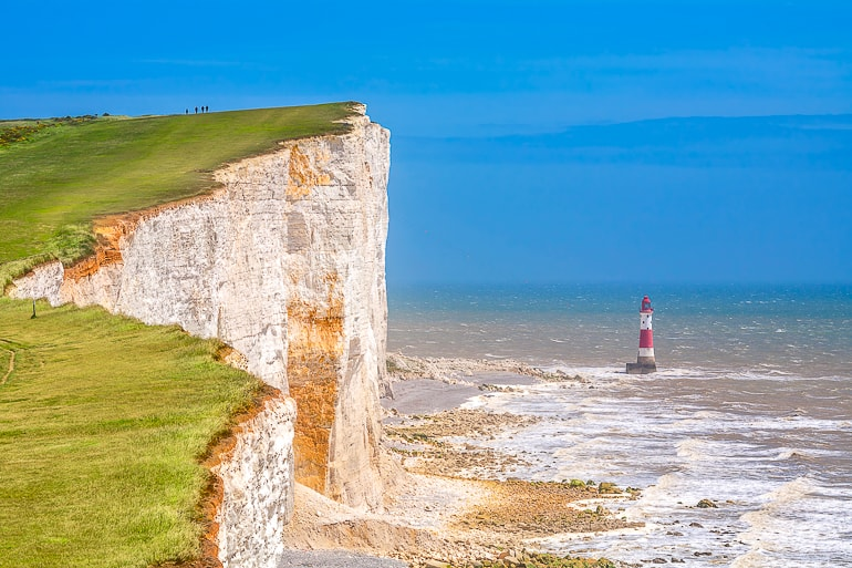 white cliff face with green grass on top and lighthouse in ocean below beachy head day trip from london
